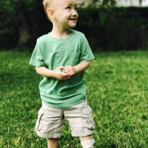 Little boy standing on his backyard, wearing a green shirt, tan shorts, white socks, white leg braces, and white shoes. he is looking to the side, smiling.