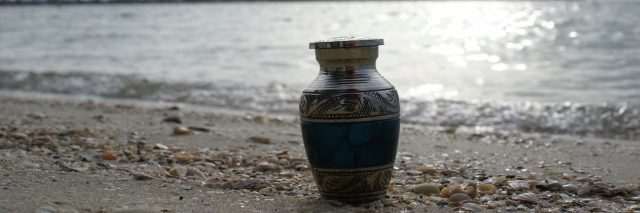 An urn on wet sand in front of a large body of water