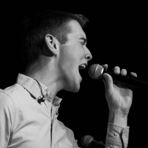 black and white photo of a young man singing