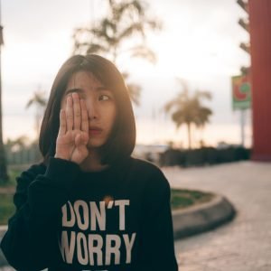 girl wearing sweatshirt that says don't worry with one hand over her face