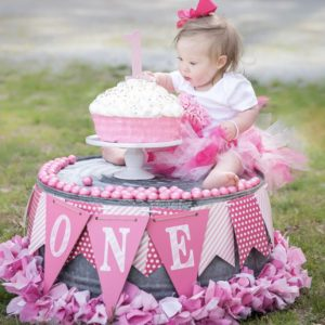 Little girl with down syndrome sitting on top of ink decorated stand and a pink birthday cake, she is reaching for the frosting