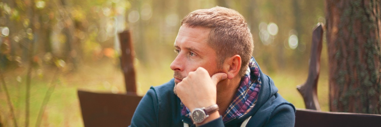 Young man sitting on a park bench contemplatively