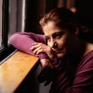 Woman wearing a long sleeve purple shirt looking outside a window, she is sad