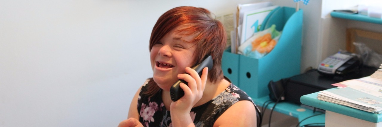 Heidi Crowter, a woman with Down syndrome, sitting ona chair, smiling, and talking on the phone