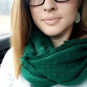 young woman wearing glasses and green scarf