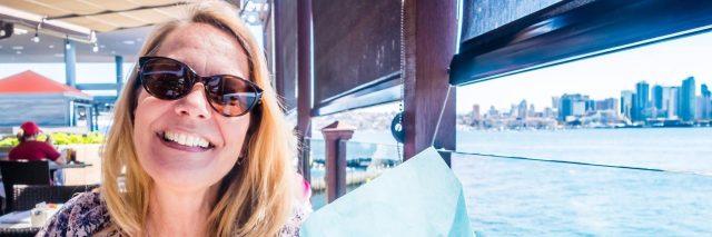 Woman wearing sunglasses, smiling by ocean