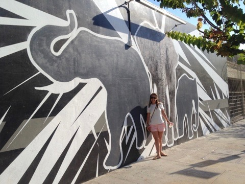 girl standing next to painting of elephants