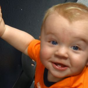 Baby with one hand raised, wearing an orange shirt