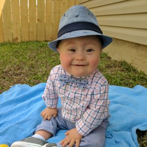 Little baby boy with Down syndrome sitting on a blue blacket outdoors. he is wearing a blue hat, plaid shirt with blue bowtie, blue jeans and blue shoes.; his Easter outfit.