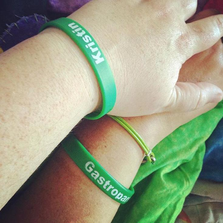 two hands wearing green gastroparesis bracelets