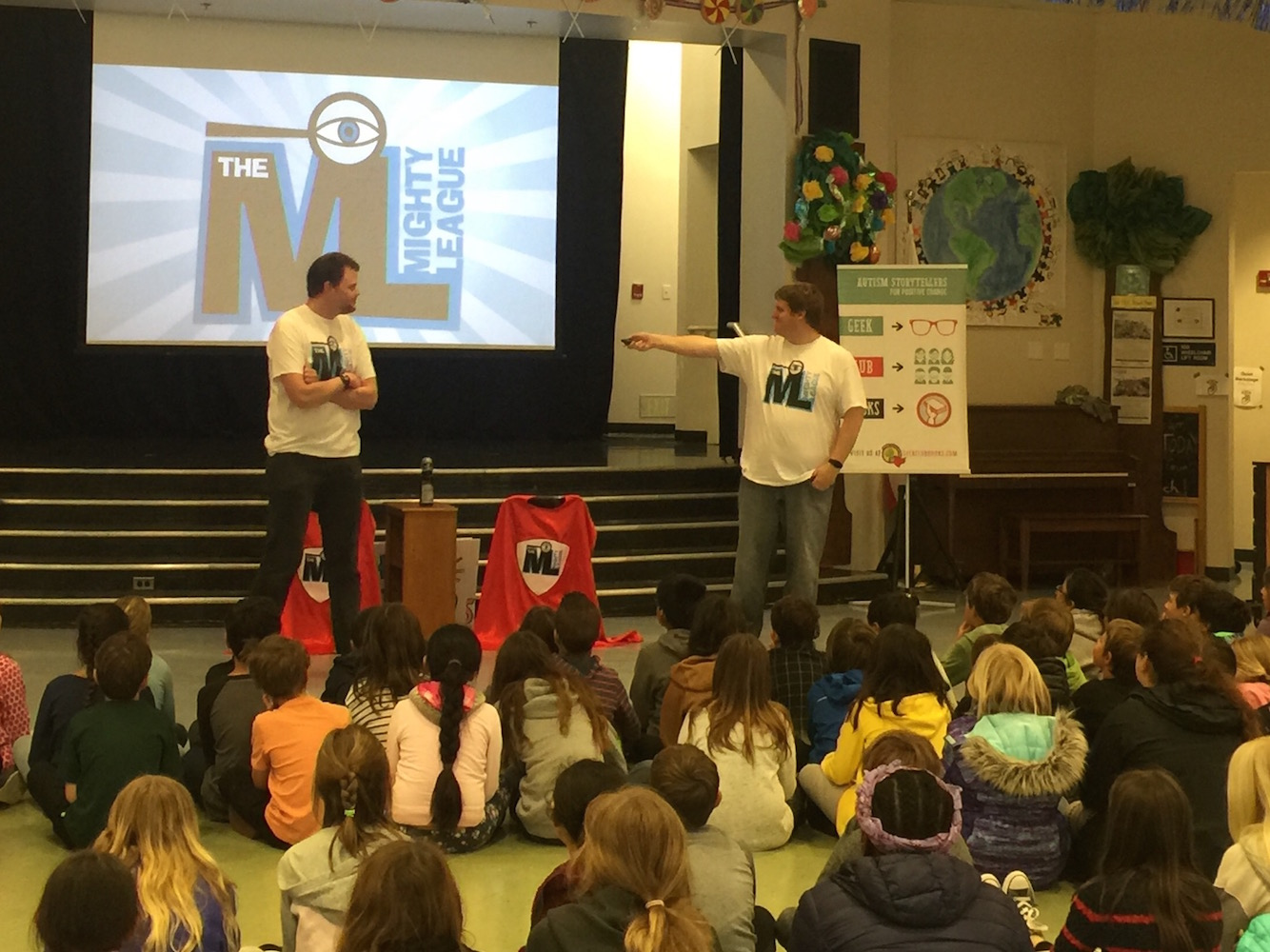 Jonathan and James at a Mighty League assembly, with children sitting and watching the presentation