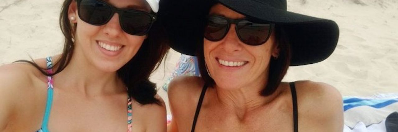 A woman and her mom wearing hats and sunglasses at the beach.