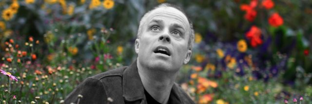 peter michael marino show up photo black and white man in colourful meadow surrounded by flowers