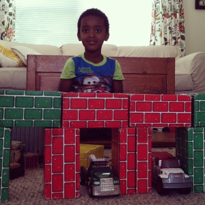 The author's son in the living room in front of stacked blocks that look like bricks