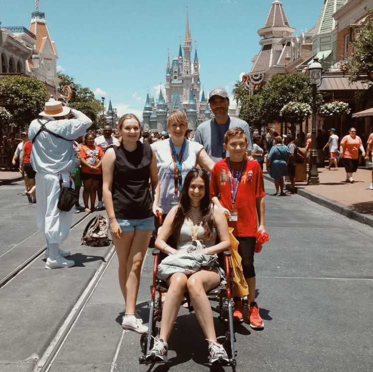 family of five posing at disneyland in front of the castle