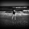 black and white photo of young girl walking along the beach