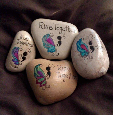 "Rocks with butterflied painted on them that say ""Rise Together"""