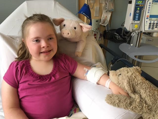 little girl in the hospital with stuffed animals