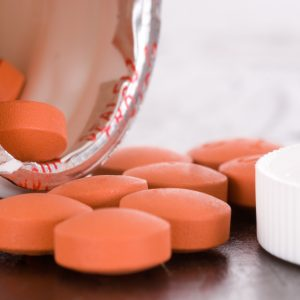 orange pills spilling out of pill bottle