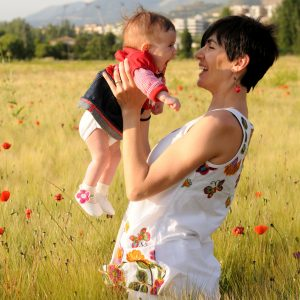 Woman smiling in a poppy field with her baby girl.