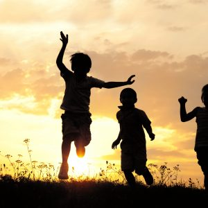 Children running in meadow at sunset.