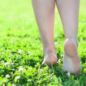 Woman stepping on grass.