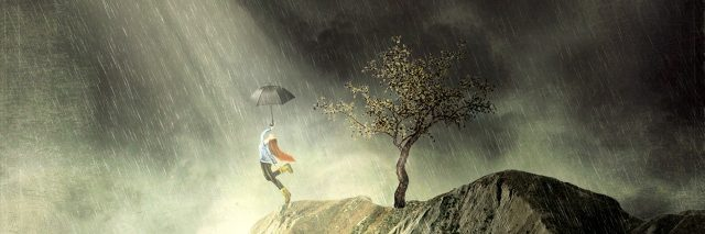 Girl on mountain dances in the rain, ray of sunshine breaking through the clouds.