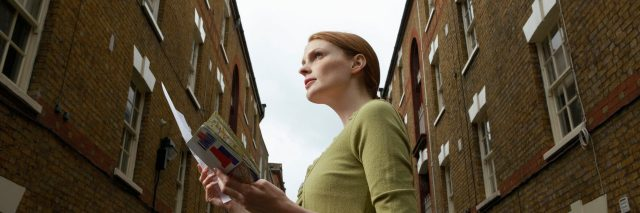 woman holding a map and standing between two brick buildings on the street