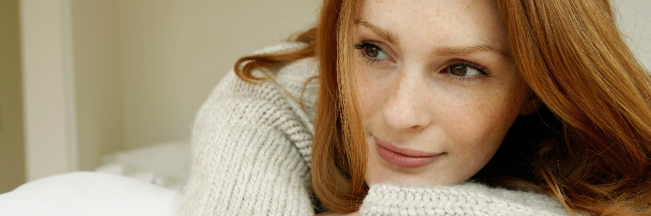 woman with red hair leaning on her arms and smiling