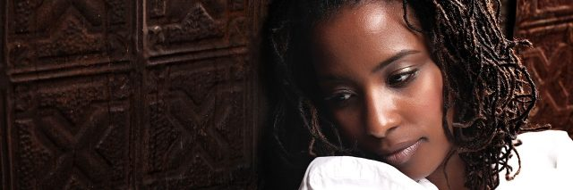 young black woman in white shirt depressed against wooden wall