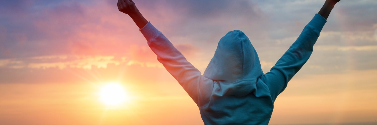 woman in blue sweatshirt raises arms victoriously in front of sunset