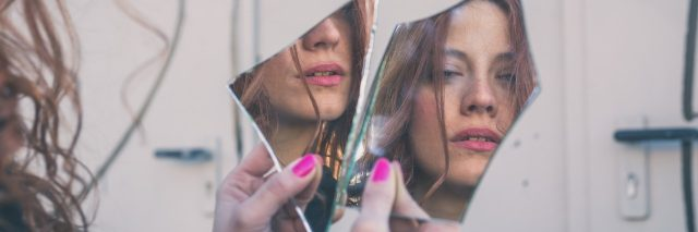 woman looking at her reflection in broken mirror pieces