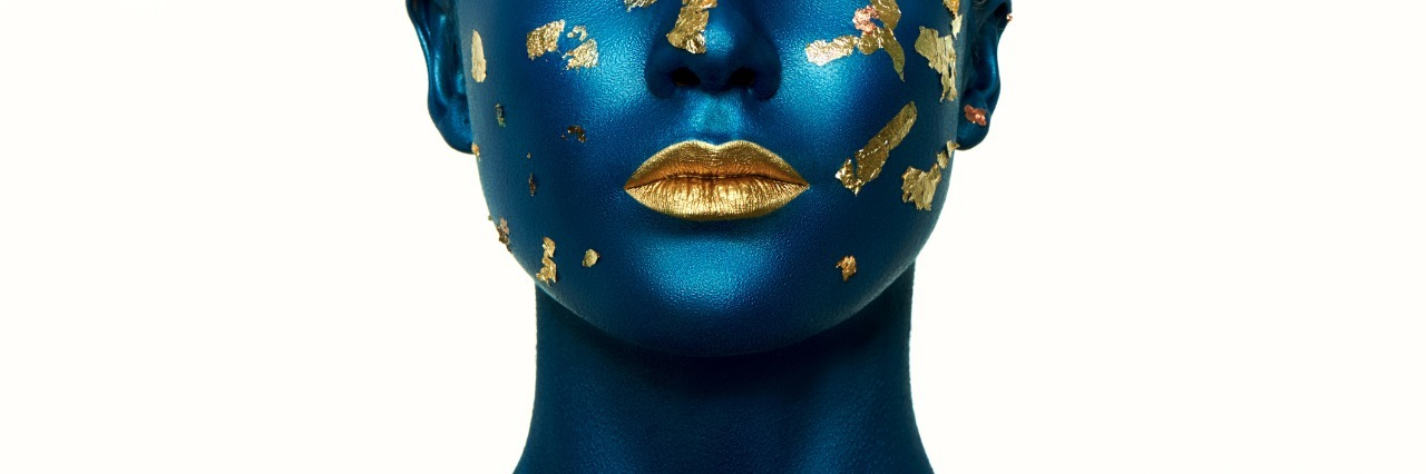 Woman painted blue, with gold specks on face and fold lipstick.
