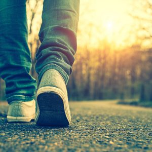 Close-up of person wearing sneakers and jeans, walking on paved path near trees