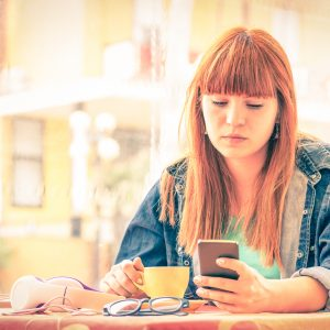 Vintage filtered portrait of serious pensive young woman with smartphone - Hipster girl using mobile smart phone
