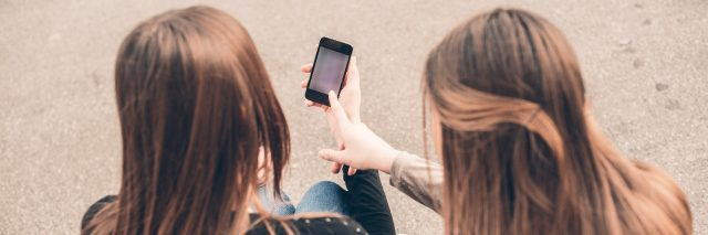 Two young women looking at mobile phone
