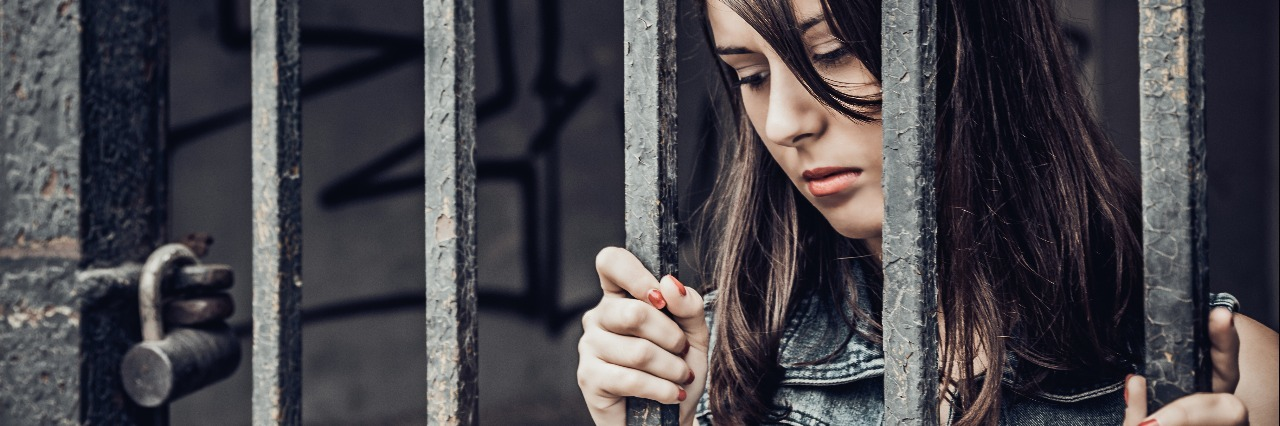 young woman trapped behind metal bars imprisoned