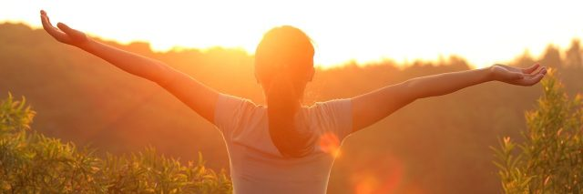 Woman standing with outstretched arms, facing sunset and tree landscape