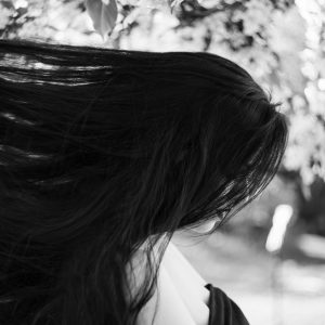 black and white image woman in garden long hair sadness