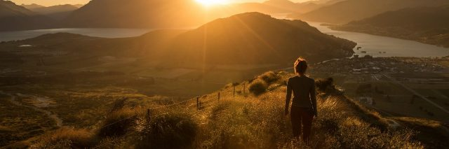 relaxed woman in new zealand mountains at sunset