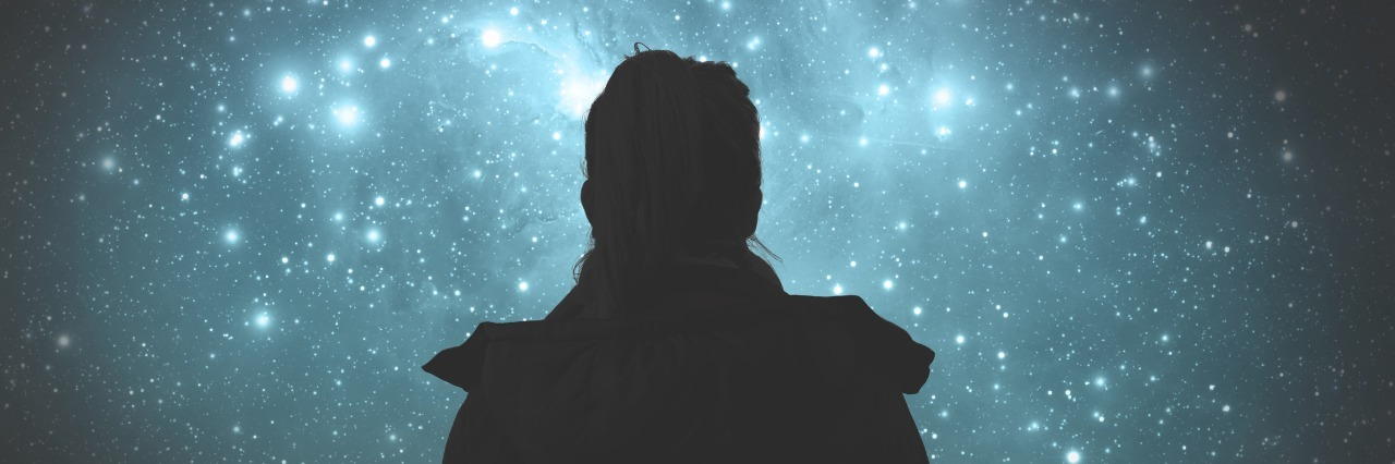 silhouette of woman looking at starry sky