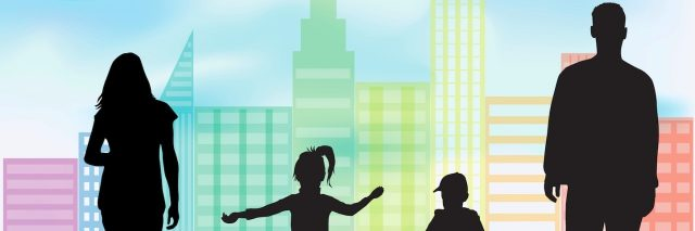 Silhouettes of man, woman, boy and girl on grass in front of city buildings