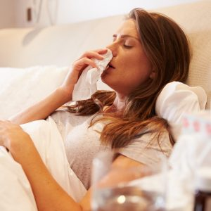 Woman in bed with a cold blowing her nose.