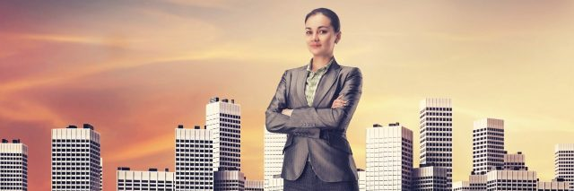 businesswoman standing among skyscrapers