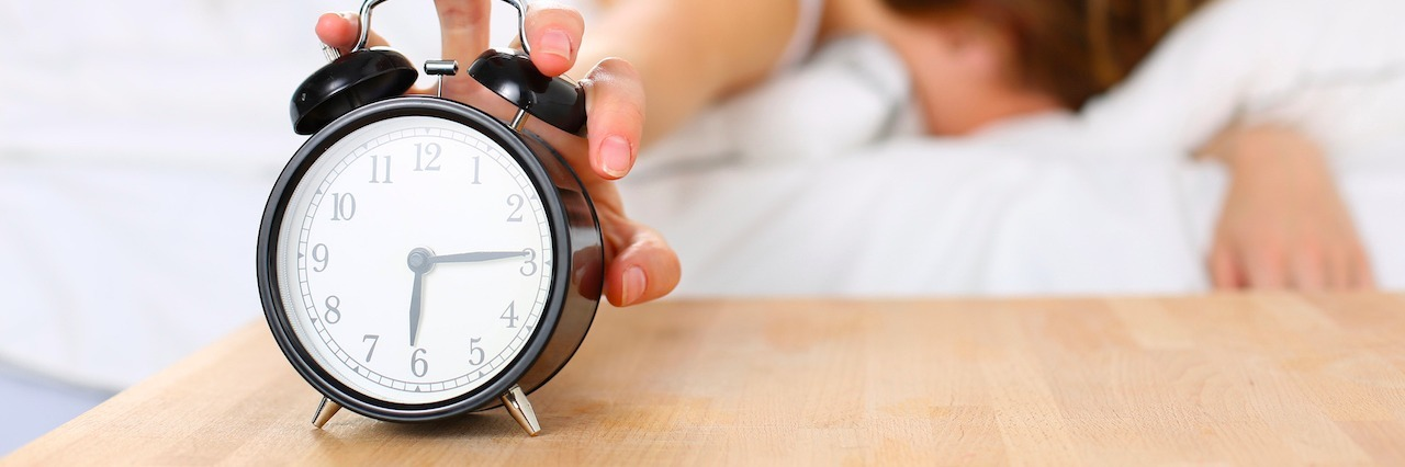 A woman touching her alarm clock