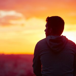 Man in front of sunrise landscape