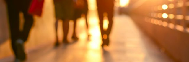 Blur silhouette of people walking on walkway in twilight
