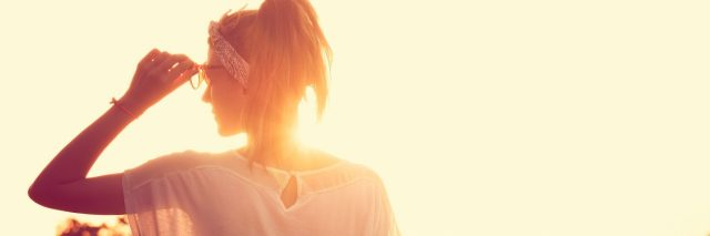 woman looking ahead with sun rising