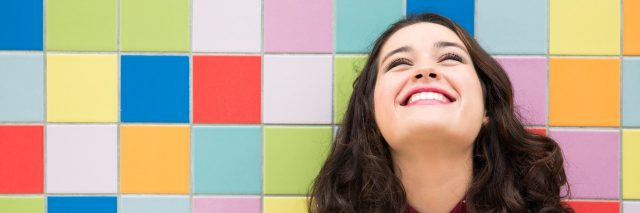 Happy girl laughing against a colorful tiles background.