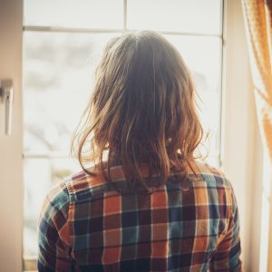 Young woman is standing and looking out the window
